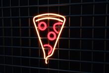 Illuminated Pizza Sign On Black Metal Grate