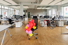Bunch Of Balloons On Chair In Open Plan Office