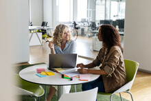 Businesswomen With Laptop Discussing At Table In Open Plan Office