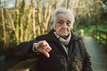 Displeased Senior Woman Showing Thumbs Down Gesture During Winter