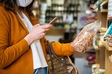 Young Woman Photographing Organic Food Package In Grocery Store