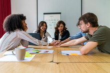 Multi-ethnic Male And Female Colleagues Stacking Hands In Board Room At Office