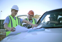 Three Construction Workers Talking Over Plans Laid Out On Car Hood