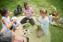 Smiling Female Friends Having Food While Sitting On Meadow