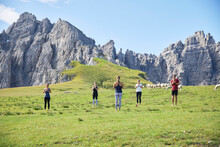 Man And Women Meditating Yoga On Meadow Against Mountain And Sky