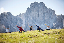 Active Man And Women Practicing Stretching Exercise Against Mountain