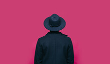 Man In Hat Standing In Front Of Pink Background