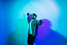 Smiling Man With Mobile Phone Dancing While Listening Music Through Headphones Against Colored Background