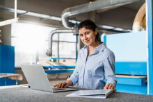 Smiling Businesswoman Using Laptop While Working At Industry