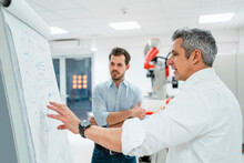 Mature Engineer Explaining Business Plans To Young Man At White Board In Factory