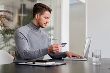 Businessman Paying Online Through Credit Card On Laptop At Office