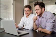 Male Entrepreneur Working On Laptop With Colleague At Office