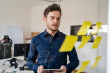Businessman Brainstorming While Looking At Adhesive Notes In Office
