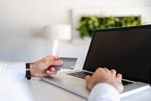 Businessman Holding Credit Card While Using Laptop At Office