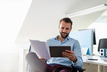 Smiling Entrepreneur With Digital Tablet And Paper Sitting At Office