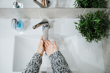 Woman Washing Hands At Sing In Bathroom