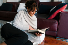Mature Woman With Eyeglasses Reading Book While Relaxing At Home