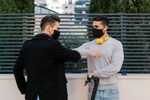 Male Friends Greeting Each Other By Giving Elbow Bump Wearing Protective Face Mask Against Metal Fence During COVID-19