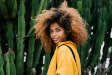 Smiling Afro Woman Standing By Cactus In Background