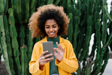 Smiling Afro Woman Using Smart Phone While Standing Against Cactus Plants