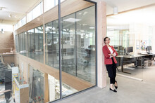 Businesswoman With Arms Crossed Leaning On Column At Office