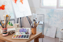Artist's Canvas And Variety Of Paintbrush On Table At Home Studio