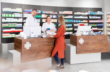 Female Customer Purchasing Medicine From Pharmacists In Store