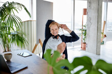 Smiling Female Entrepreneur With Hands Behind Head Relaxing On Chair At Desk In Home Office