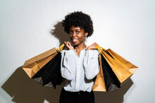 Smiling Young Woman Carrying Shopping Bags While Standing Against White Background