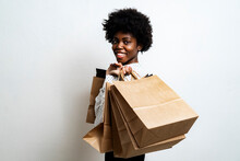 Smiling Woman Carrying Shopping Bags While Standing Against White Background