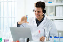 Smiling Young Scientist Showing Test Tube During Video Call On Laptop In Laboratory