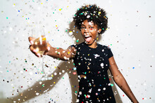 Cheerful Woman With Champagne Flute Standing Amidst Confetti Against White Background
