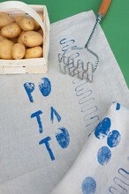 Basket Of Raw Potatoes, Potato Masher And Fabric Covered In Blue Prints