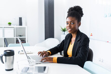 Young Afro Businesswoman Using Laptop While Sitting At Desk In Office