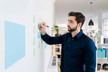 Young Businessman Writing Strategies On Adhesive Notes At Wall In Office