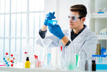 Young Scientist Measuring Chemical In Flask At Laboratory