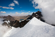 The Cloudy Views Reveal Mountains And More Glaciers On The Snow-covered Summit Of Mt. Pequeno Alpamayo Bolivia's Cordillera Real.