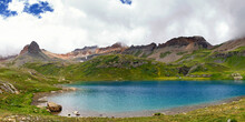 The Beautiful Turquoise Waters Of Ice Lake Near Silverton, Colorado Glow Even In The Shade Of The Clouds.