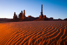 Monument Valley's Totem Pole And Surrounding Sandstone Towers Above Wind Swept Sand Dunes.