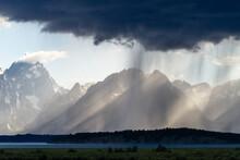 Light Rays Break Through Storm Clouds Hitting Rain Above The Teton Mountains In Grand Teton National Park, Wyoming.