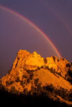 A Double Rainbow Arches Over The Presidents Of Mount Rushmore, South Dakota.
