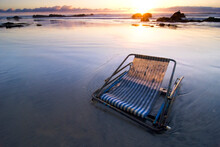 An Abandoned Beach Chair Is Illuminated At Sunset On La Fonda Beach In Baja, Mexico.
