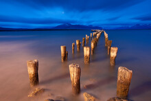 Wooden Pillars Of An Old Pier Stand Motionless Against A Turbulent Sky In Puerto Natales, Patagonia, Chile.