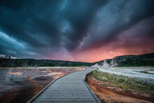 Evening Storm Clouds Gather Over A Boardwalk In Biscuit Basin, Yellowstone National Park.