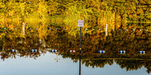In The Morning Light, A Caution Sign And Shoreline Vegetation Are Reflected In The Russian River At Healdsburg Veterans Memorial Beach Park.