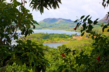 Huahini, French Polynesia: View Of Bay Taken From Mountains Of Huahini Island With Lush, Tropical Greenery Framing The Water.