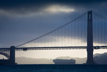 Sunset Behind The Golden Gate Bridge In San Francisco, CA Under Cloudy Skies As Ships Head Out To Sea.
