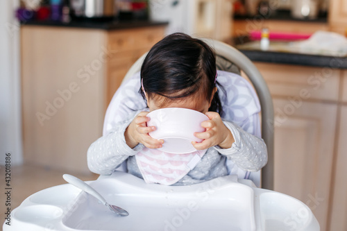 Fotografie, Obraz Funny Asian Chinese kid girl sitting in high chair eating drinking soup from plate bowl