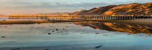 The Rising Sun Lights Up The Pismo Beach Pier And Surrounding Hills Creating A Reflection In The Shallow Pool Of Water.