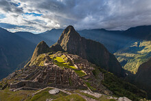 Light Streams Through The Clouds And Lights Parts Of The Ancient City Of Machu Picchu.